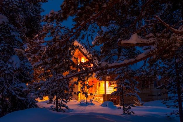 Wieczorny zimowy las. gałęzie sosnowe pokryte dużymi czapami śniegu. oświetlony domek w tle