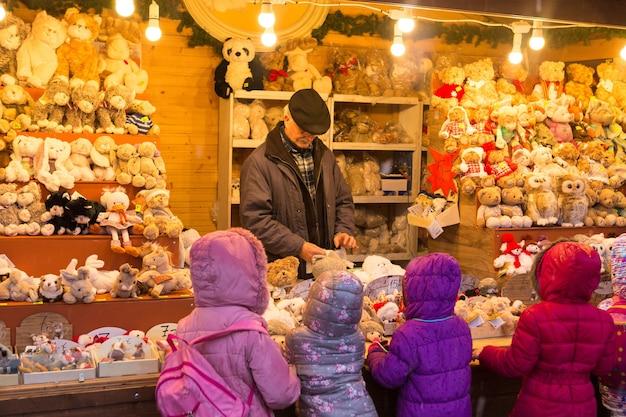 Wiedeń austria świąteczne pamiątki w europie starszy mężczyzna pokazuje dzieciom świąteczne zabawki