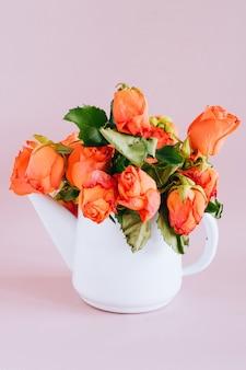Więdnąca róża pomarańczowa w emaliowanym czajniku