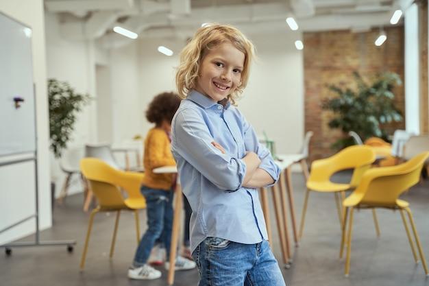 Wiedz to wszystko portret wesołego chłopca uśmiechającego się do kamery stojącej z rękami skrzyżowanymi podczas pozowania dla
