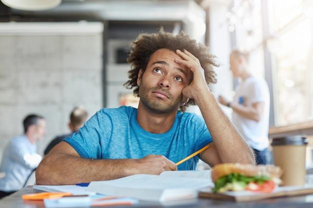 Wiedza i edukacja. niezadowolony afroamerykański student uniwersytetu w niebieskiej koszulce patrząc w górę z wątpliwym sfrustrowanym wyrazem twarzy, czując się zmęczony podczas pracy w domu w kawiarni