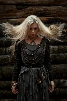 Wiedźma w długiej czarnej sukience spacerująca po wiosce w ciemności