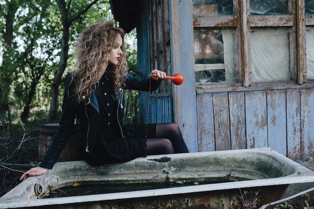 Wiedźma w stylu vintage odprawia magiczny rytuał z eliksirem w ręku w przeddzień halloween