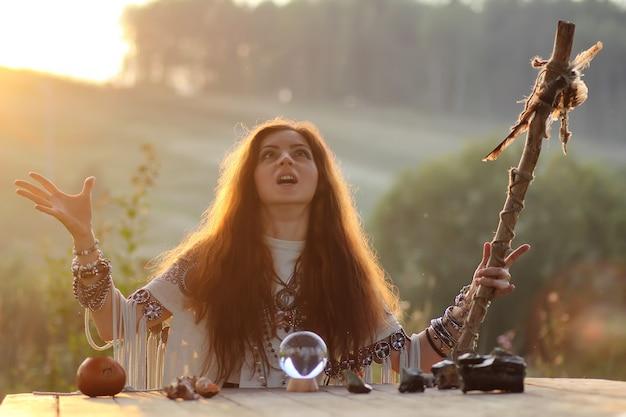 Wiedźma z kryształową kulą o zachodzie słońca