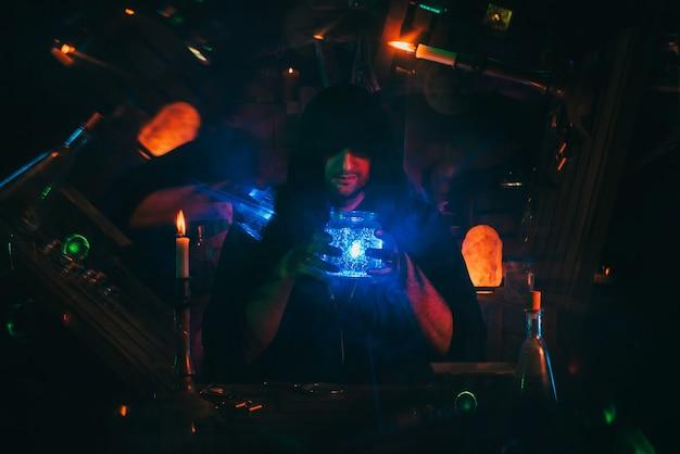 Wiedźmiński alchemik robi sekretną miksturę w ponurym laboratorium. mroczny mag czarownik w kostiumie na halloween przy stole