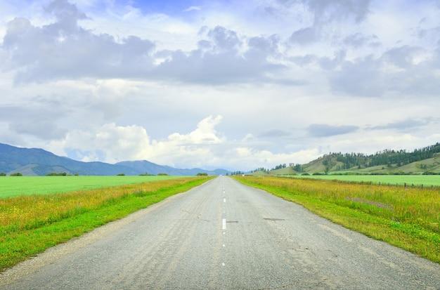 Wiejska autostrada otoczona górami latem pod błękitnym pochmurnym niebem. syberia, rosja