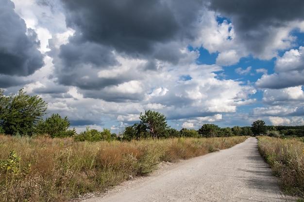 Wiejska droga do lasu przez pole przy dramatycznie zachmurzonym niebieskim niebie
