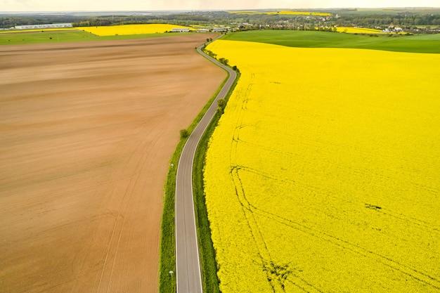 Wiejska droga oddzielała puste i żółte pola rzepaku ze wzorem pozostawionym przez kombajn. widok z góry pola rolnicze na wiosnę.