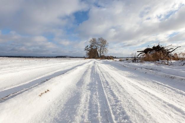 Wiejska droga pokryta śniegiem zimą. są ślady samochodu. na tle błękitnego nieba.