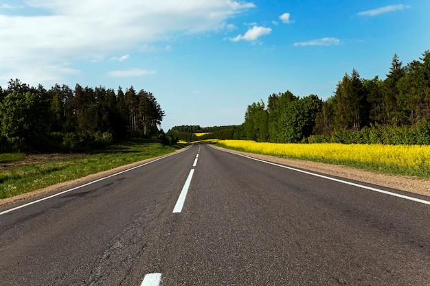 Wiejska droga przechodząca w pobliżu pola, na którym uprawiano rzepak