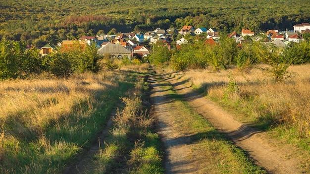 Wiejska droga w jesieni pola niebieskim niebie. polna droga przez pola.