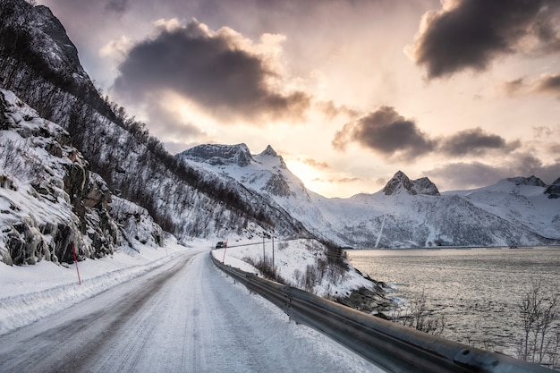 Wiejska droga w śnieżnej dolinie na wybrzeżu zimą o zachodzie słońca