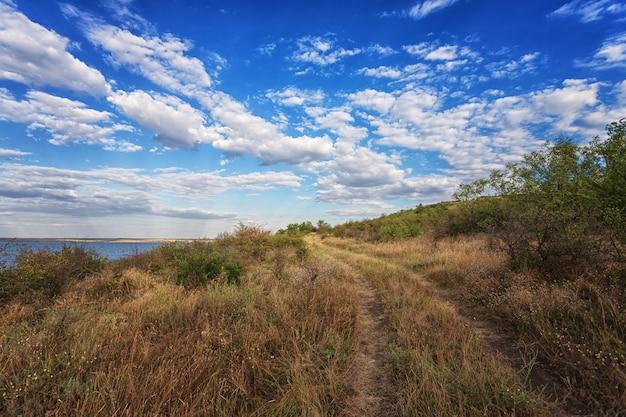 Wiejska droga, wzdłuż rzeki, jeziora, porośnięta trawą i krzewami