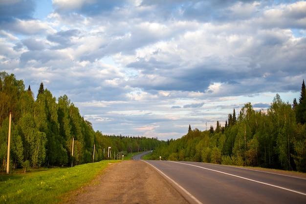Wiejska droga z oznaczeniami w środku lasu. ścieżka i ruch do przodu na słońcu. piękny, zielony las na wiosnę o zachodzie słońca. koncepcja sukcesu w przyszłym celu i upływającym czasie