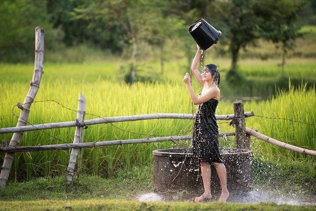 Wiejska dziewczyna bierze prysznic z tradycyjnego stawu groundwater