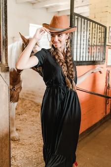Wiejska dziewczyna w koniu zszywek na farmie na ranczo