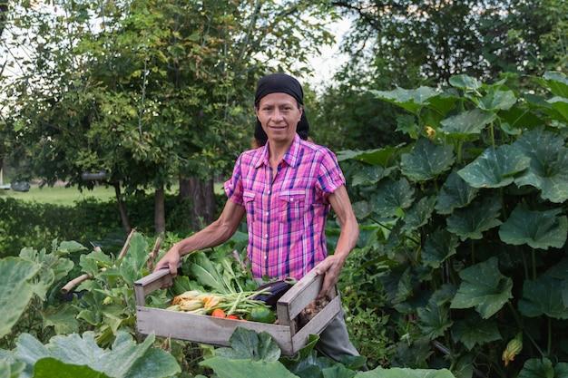 Wiejska kobieta ze zbiorami warzyw z ekologicznego ogrodu w drewnianej skrzyni