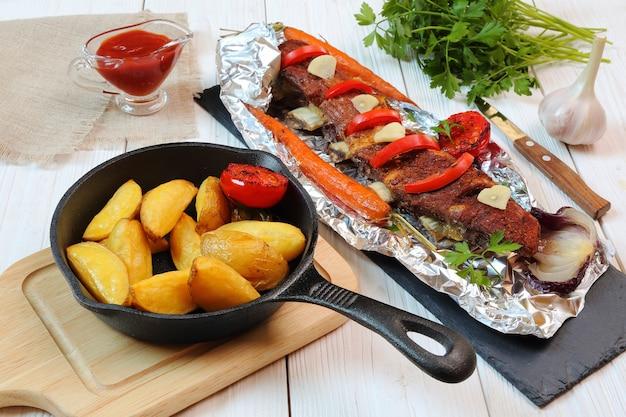 Wiejska kolacja - pieczone kotlety cielęce z warzywami i ziemniakami na białym drewnianym stole