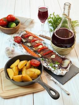 Wiejska kolacja - pieczone kotlety cielęce z warzywami, ziemniakami i czerwonym winem na białym drewnianym stole
