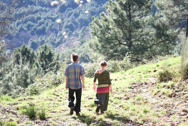 Wiejska para spaceru po górach na plecach w pięknym krajobrazie.