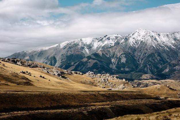 Wiejska scena na wyspie południowej nowej zelandii brzmiała przez góry pokryte śniegiem