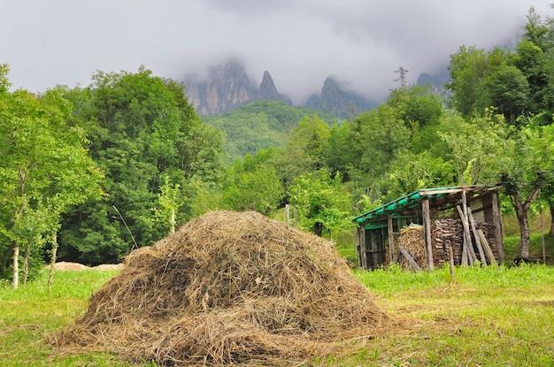 Wiejska scena w włoskich dolomit górach z stosem słoma w łące