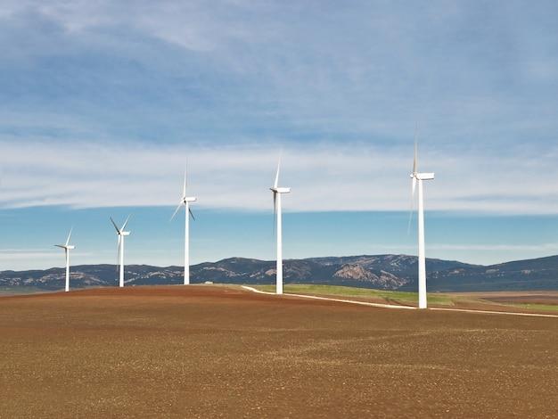 Wiejska scena z wiatrakami generatorów elektrycznych w pochmurny dzień