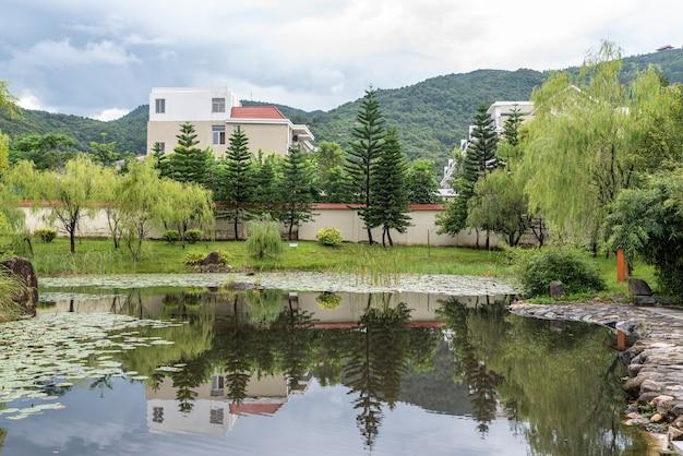 Wiejska sceneria po deszczu, domy, zielone góry i rzeki