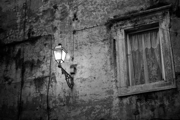 Wiejska ściana z lampą w nocy