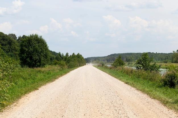 Wiejska szutrowa droga, na horyzoncie widać kurz z przejeżdżających samochodów, letni krajobraz