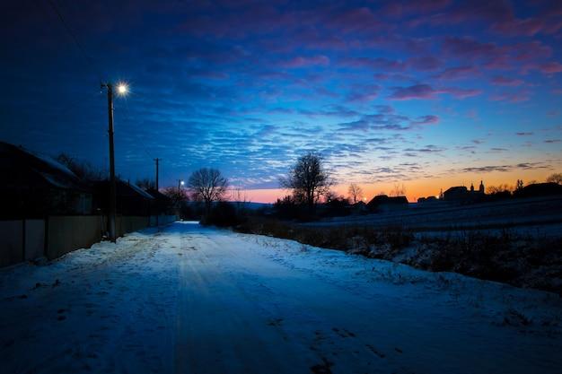 Wiejska ulica wieczorem podczas zachodu słońca przy świetle latarni_