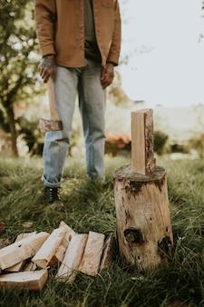 Wiejski człowiek rozłupuje drewno siekierą na polu