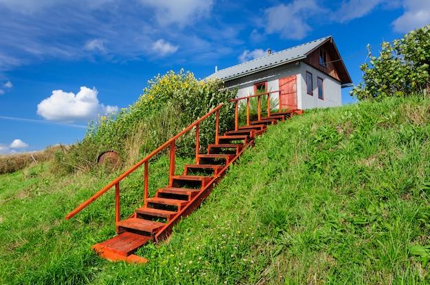 Wiejski dom na wzgórzu, ze schodami