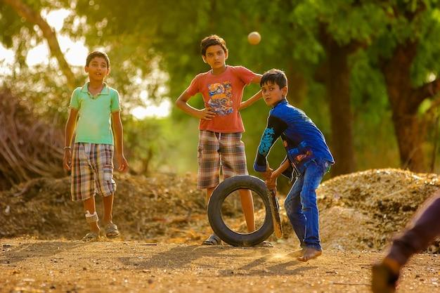 Wiejski indiański dziecko bawić się krykieta na ziemi