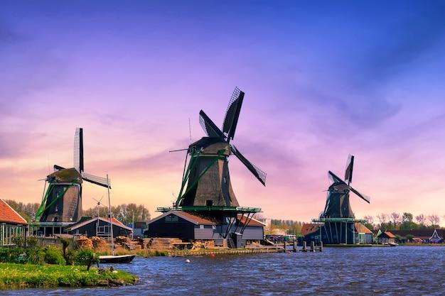 Wiejski krajobraz holandii. tradycyjne holenderskie wiatraki z kanałem w wiosce zaanse schans podczas zachodu słońca.