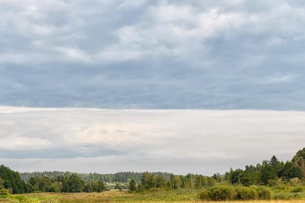 Wiejski krajobraz na chmurnym szarym nieba tle