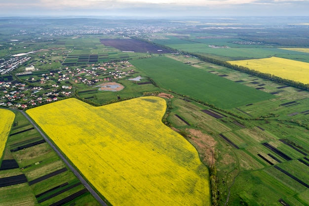 Wiejski krajobraz na dzień wiosny lub lata. widok z lotu ptaka na zielone, zaorane i kwitnące pola, dachy domów w słoneczny świt. fotografia dronów.