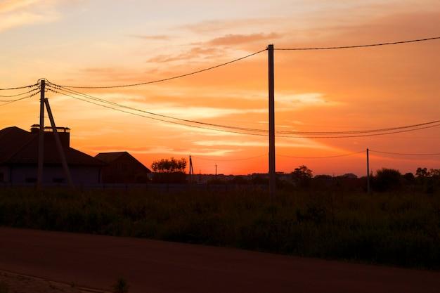 Wiejski krajobraz o zachodzie słońca. ustawienie słońca, domów, dróg i linii elektrycznych na jasnym pomarańczowym tle nieba.
