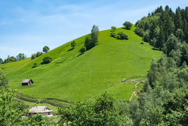 Wiejski krajobraz, wzgórza i błękitne niebo. pastwiska zielonych łąk. ekoturystyka.