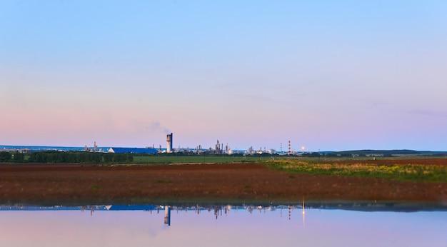 Wiejski krajobraz z zakładem chemicznym na horyzoncie odbity w rozmytym pierwszym planie wody