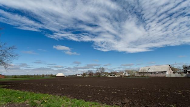 Wiejski krajobraz z zaoraną ziemią i gospodarstwem