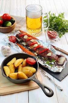 Wiejski obiad - pieczone kotlety cielęce z warzywami, ziemniakami i piwem na białym drewnianym stole