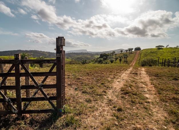 Wiejski obraz na farmie z drewnianą bramą, polną drogą, słońcem i wzgórzami w tle.