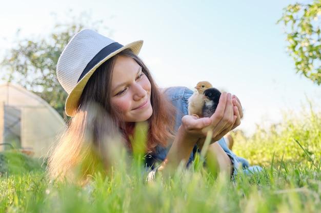 Wiejski styl rustykalny, piękna uśmiechnięta nastolatka z nowonarodzonymi kurczakami