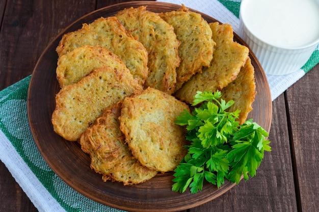 Wiejskie naleśniki wegetariańskie z ziemniaków w glinianej misce. widok z góry