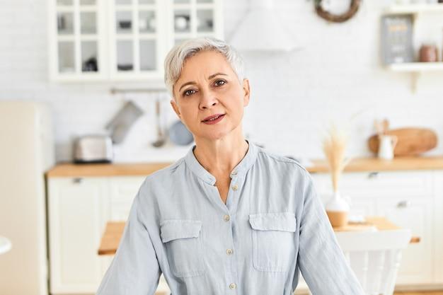 Wiek, dojrzałość, domostwo i styl życia. kryty ujęcie niedbale ubrana emerytka o zmęczonym wyglądzie, wydychająca powietrze po wykonaniu wszystkich prac domowych, pozująca na rozmytym wnętrzu kuchni