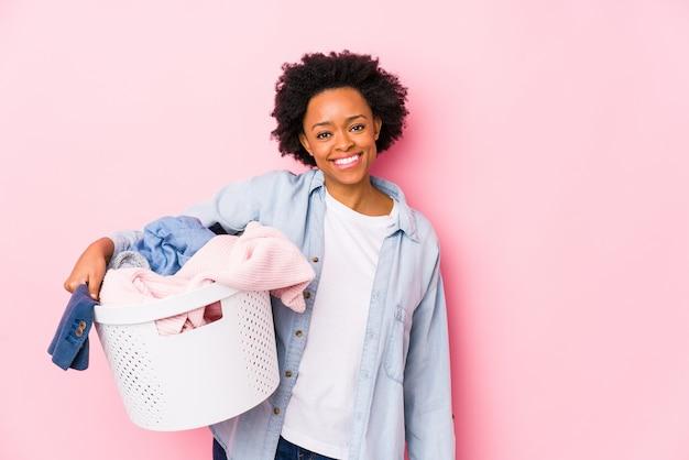 Wiek średni amerykanin afrykańskiego pochodzenia kobieta robi pralni odizolowywał ono uśmiecha się ufny z krzyżować rękami.
