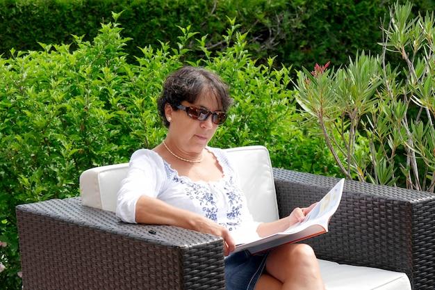Wiek średni kobieta czyta książkę siedzi w domu w ogródzie