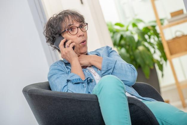 Wiek średni kobieta z szkłami używać telefon i opowiadający