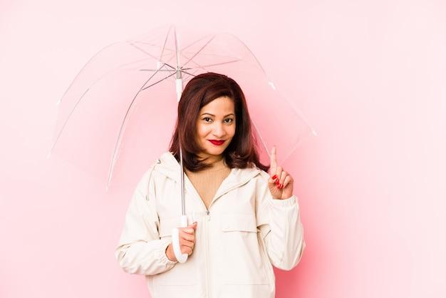 Wiek średni łacińska kobieta jest ubranym parasol odizolowywał pokazywać liczbę jeden z palcem.